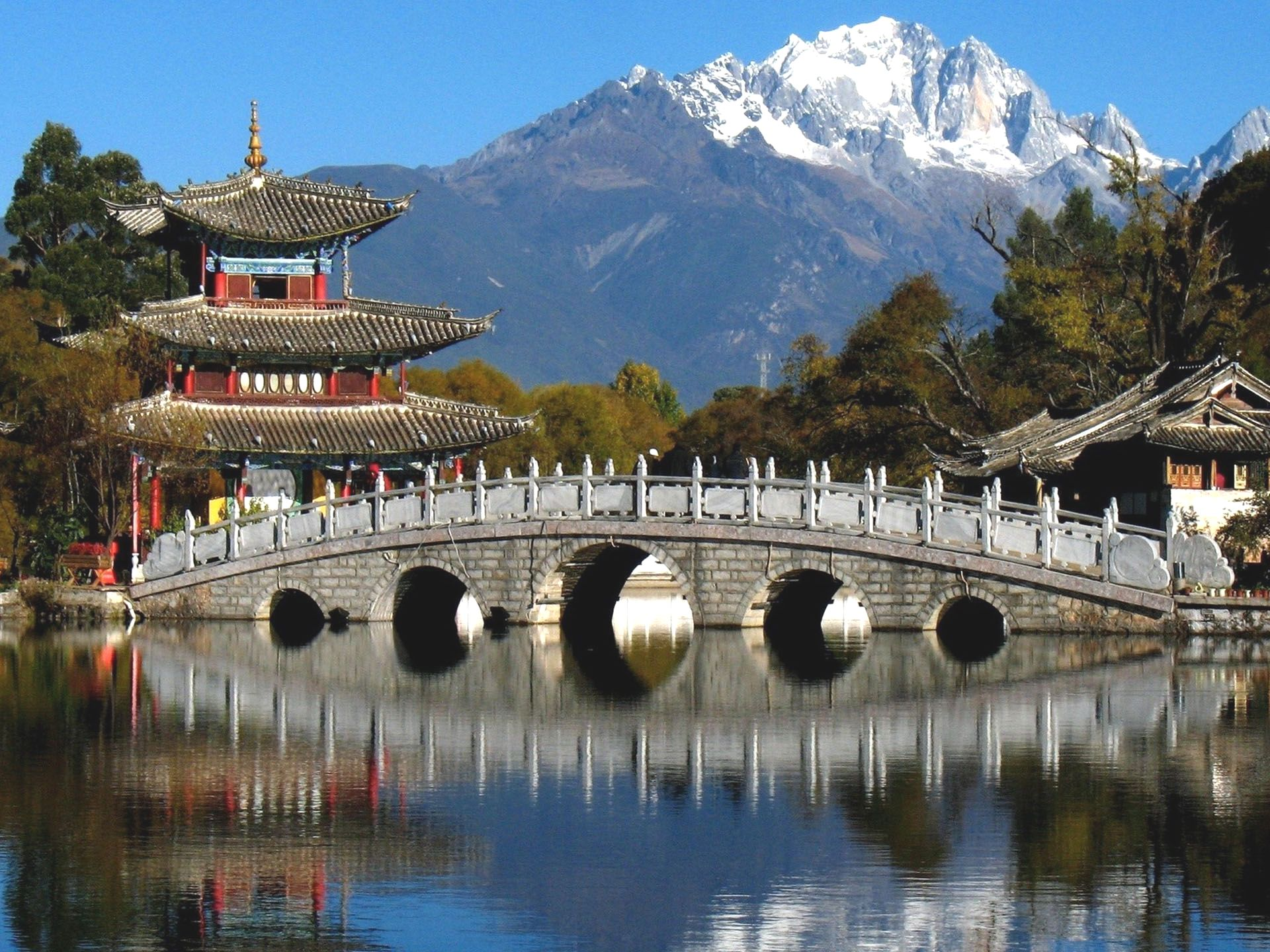 Chinese Temple and a Bridge over a Lake in China with Snow-Capped Mountains in the Background