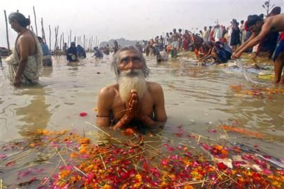 Man Praying in the River Ganges in India