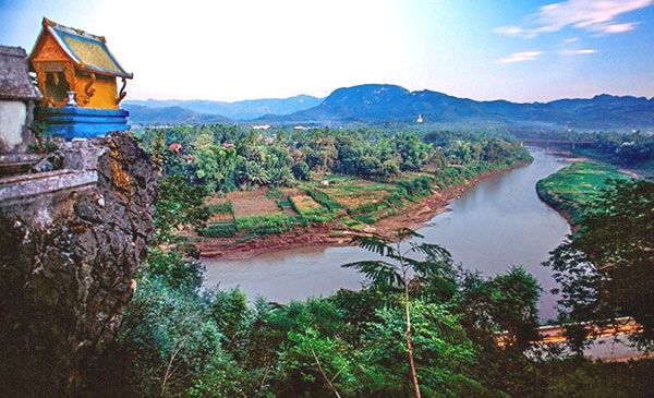 Aerial View of One of the Main Rivers in Laos with a Temple on the Cliff Overlooking
