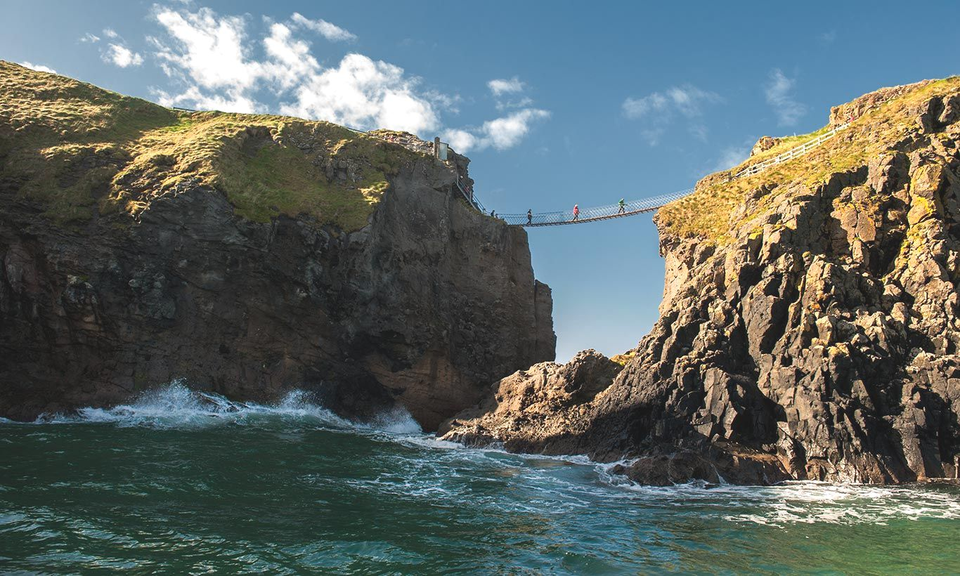 Tourists Crossing a Tiny Walkway between 2 Cliffs by the Sea in Northern Ireland