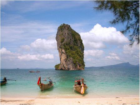 Famous Rock in the Sea in Thailand with Fishing Boats